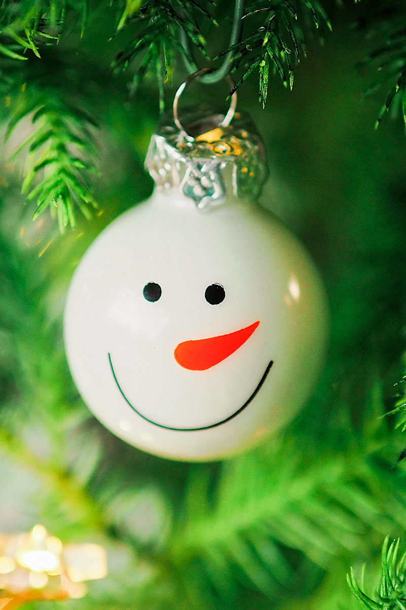 close up picture of a smiling snowman Christmas ornament on a tree