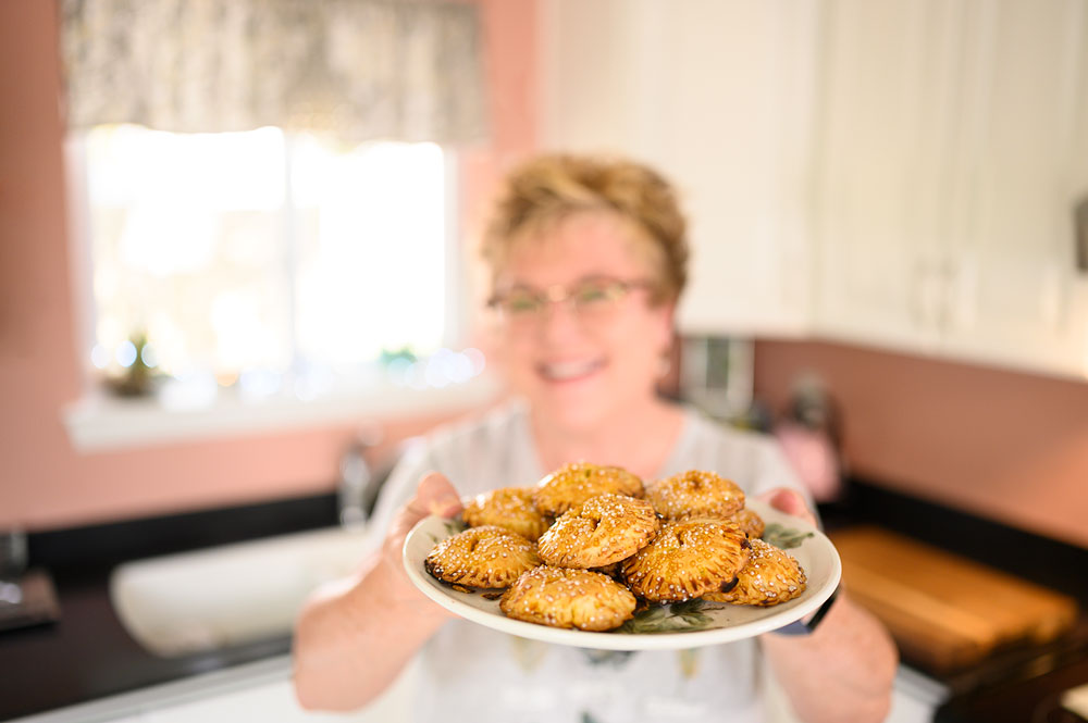 smiling person serving a dish of pumpkin hand pies