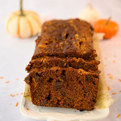 sliced pumpkin bread with orange pumpkins in background