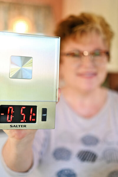 woman holding a food scale