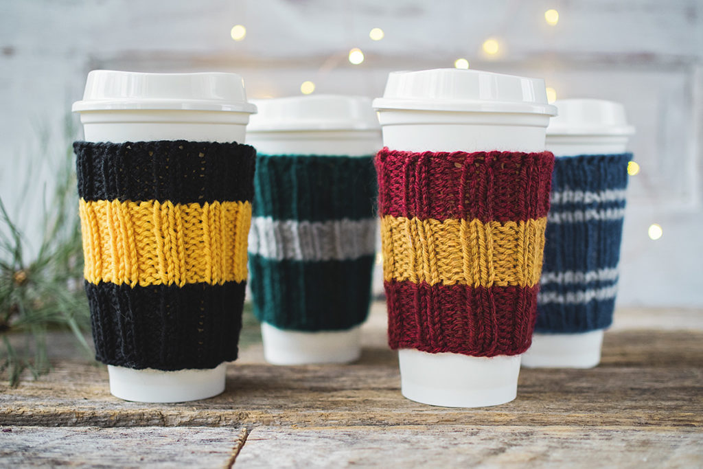 four travel coffee cups wearing different knitted sleeves
