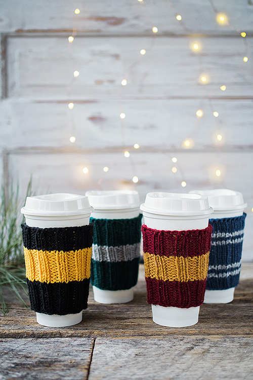 four travel cups all wearing knitted sleeves
