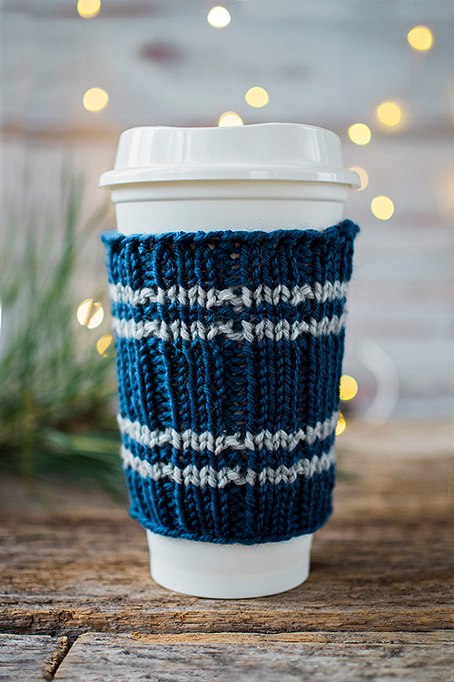 close up of travel cup fitted with a knitted sleeve