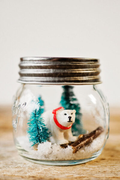 waterless snow globe with a polar bear, bottle brush trees and fake snow.
