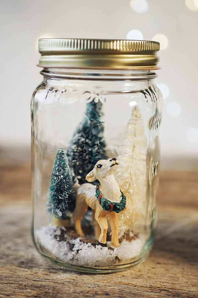 miniature deer and bottle brush trees in a mason jar