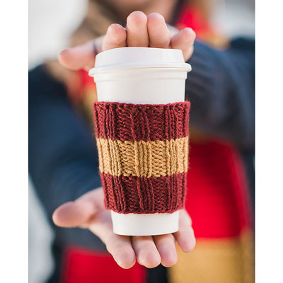 hands holding a travel coffee cup in a hand knit coffee cozy