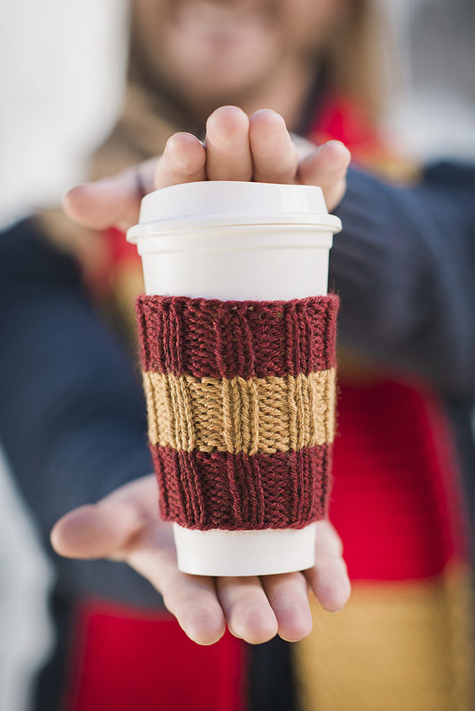 closeup of hands holding a travel coffee cup wearing a knitted coffee sleeve