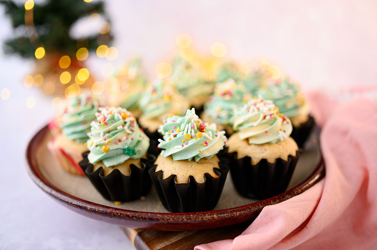 tray of a dozen piped cupcakes with sprinkles in front of a small Christmas Tree with twinkling lights