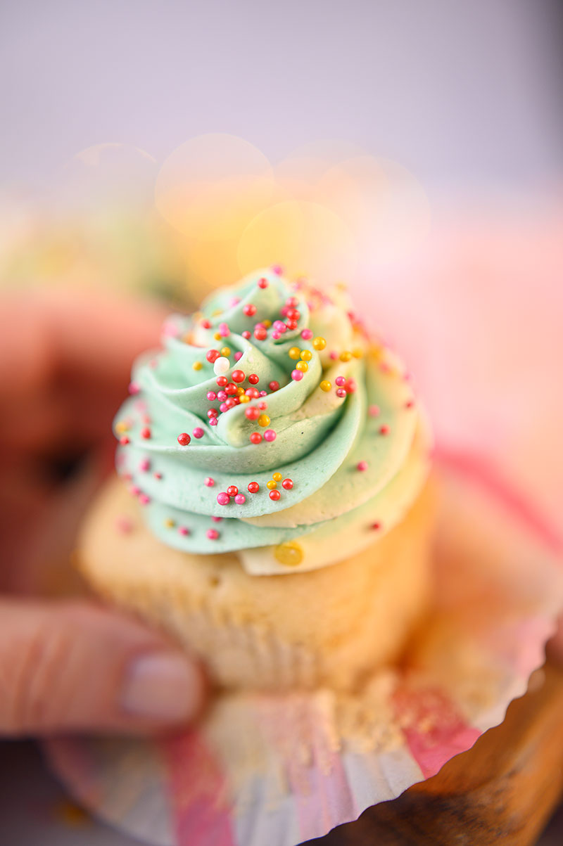 Close up of a hand holding a piped cupcake with light green frosting and pink and red sprinkles.
