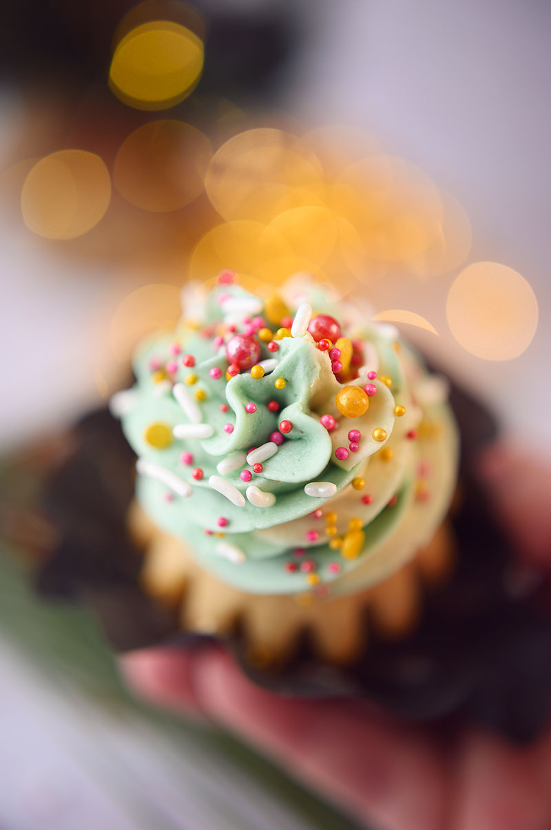 very close up, overhead view of the beautiful light green frosting swirled on a vanilla cupcake