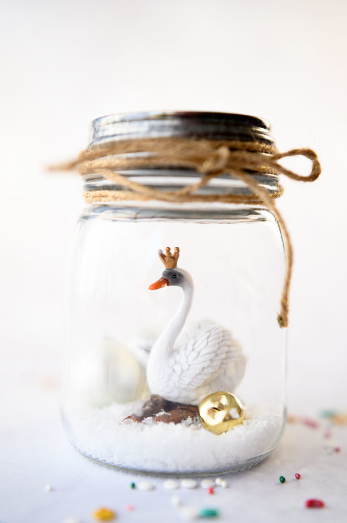 a white swan wearing a crown inside a mason jar with fake snow and jingle bells