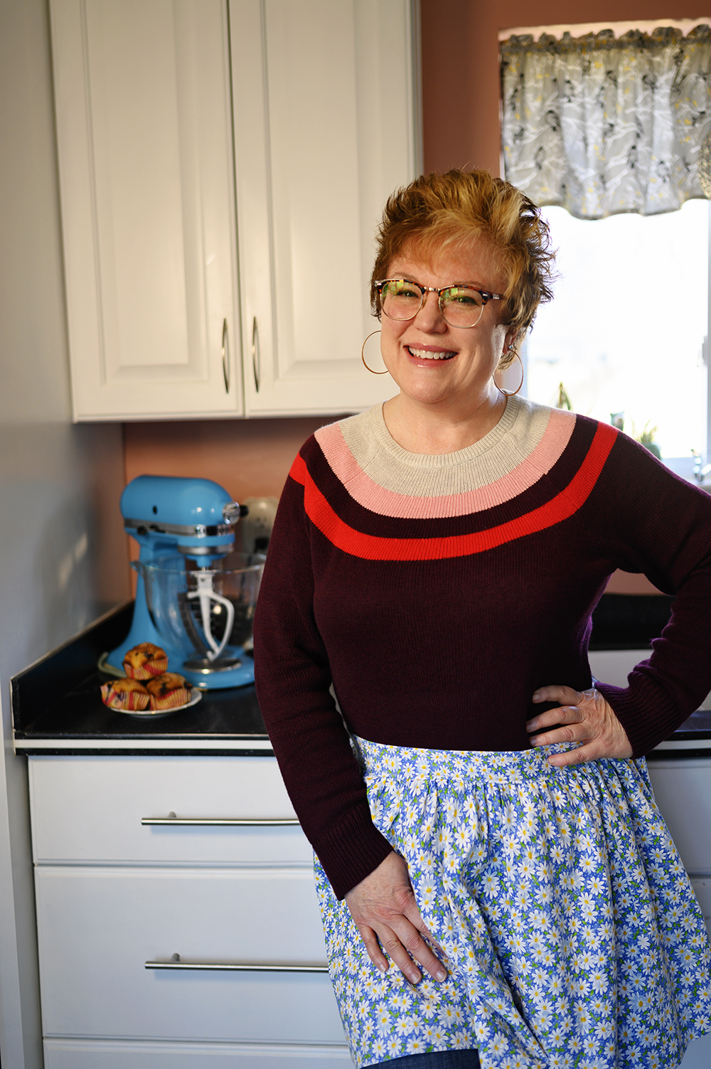 smiling woman wearing an apron in a home kitchen