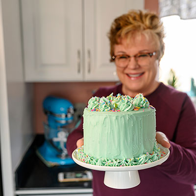 smiling woman holds a small layer cake