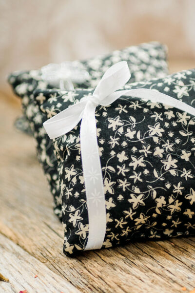 two small sachets sewn in a black and cream floral print with a white ribbon tied in a bow
