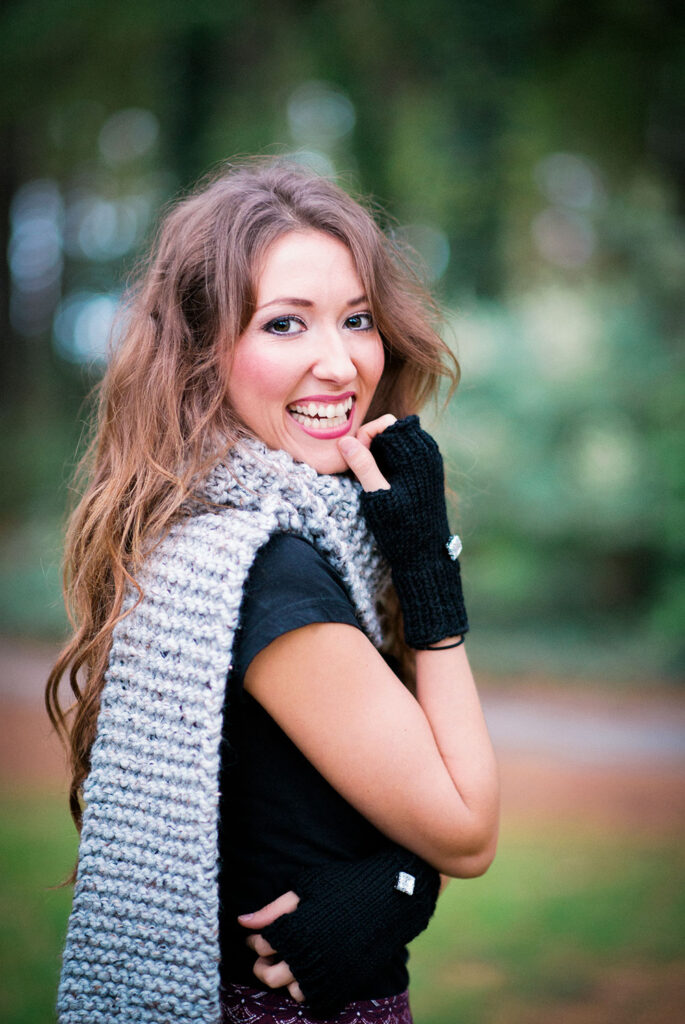smiling young woman shows off a chunky knitted scarf