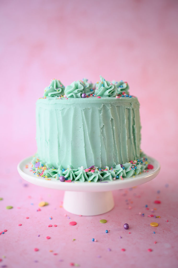 pretty layer cake with mint green frosting and colorful sprinkles