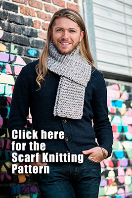 stylish young man demonstrates a wrapped scarf around his neck posing in from of a street art mural