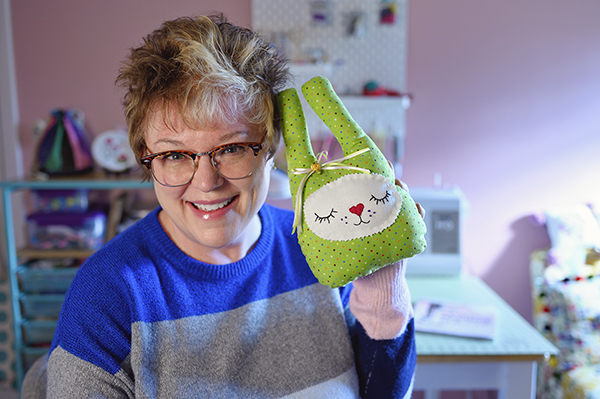 Woman holds a green bunny toy, handmade with her sewing machine also pictured.