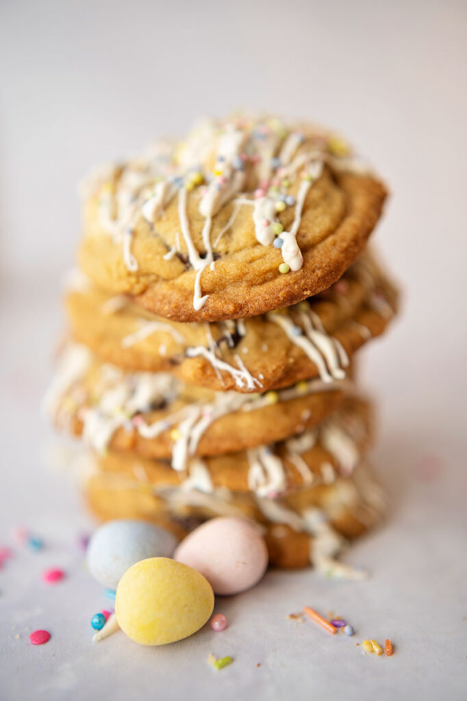 tall stack of cookies covered in white chocolate drizzle and sitting with mini candy coated pastel Easter eggs and colorful sprinkles
