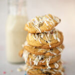stack of easter cookies with a small bottle of milk
