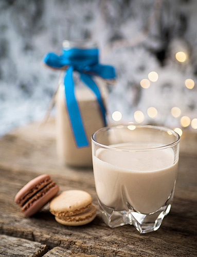 glass with Irish cream with macarons and a milk bottle with more cream