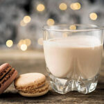 a glass of IRish cream posed with 2 macarons