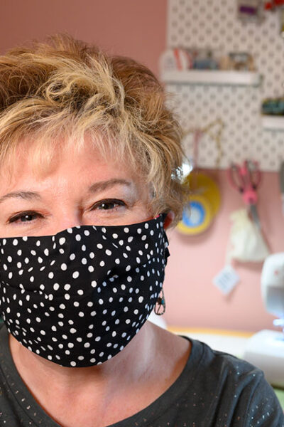 front facing view of a woman wearing a polka dot pleated face mask