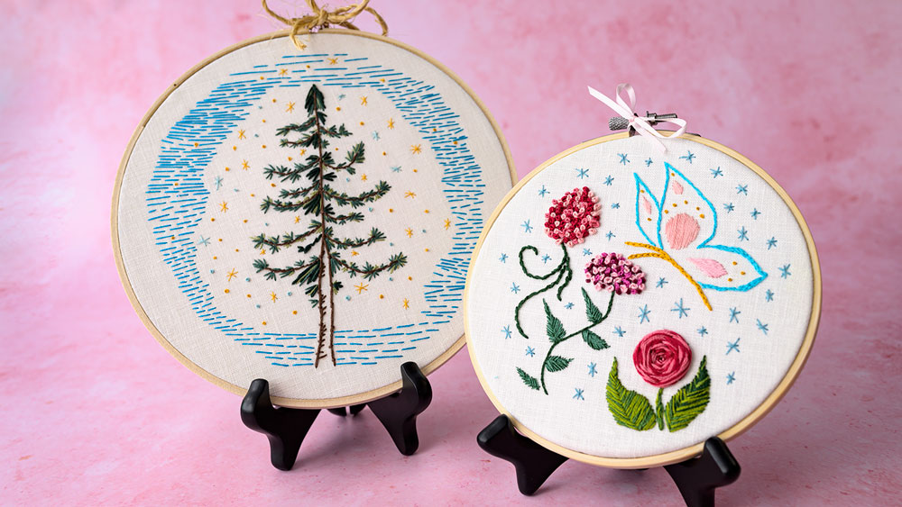 Two embroidery projects sitting side by side. One is a stitched pine trea and the other is a flower sampler with a butterfly