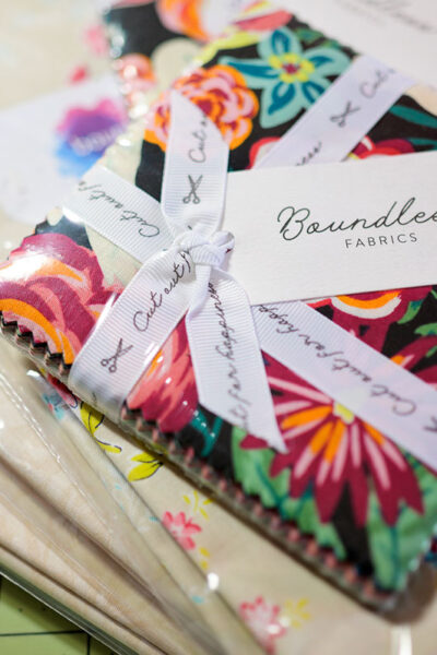 Overhead image of a stack of bright Charm Square fabric on a stack of neutral yardage.