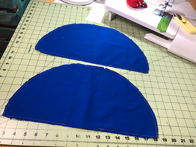two dark blue half circles of fabric on a sewing table to demonstrate the stitch line for sewing the christmas tree napkins as well as the cutting and clipping done to reduce bulk when the projects are turned right side out