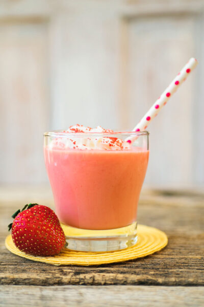 A glass of pink strawberry daiquiri is topped with whipped cream and a pink polka dotted straw. There is a fresh whole strawberry next to the glass for garnish.
