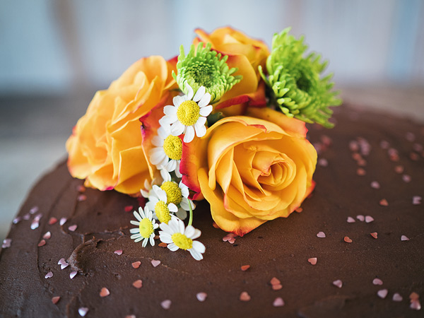 closeup of the roses and daisies floral arrangement made to decorate the chocolate cake