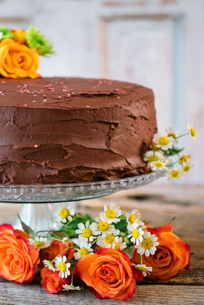a large chocolate layer cake sits on a glass pedestal cake stand decorated with small white daisies and orange roses.