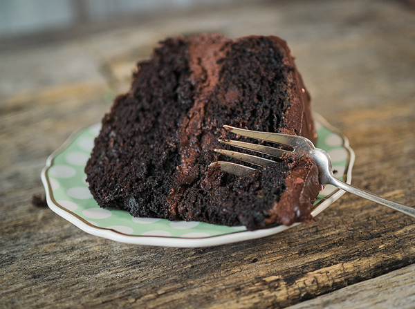 a slice of chocolate layer cake on a plate with a fork ready to take a bite
