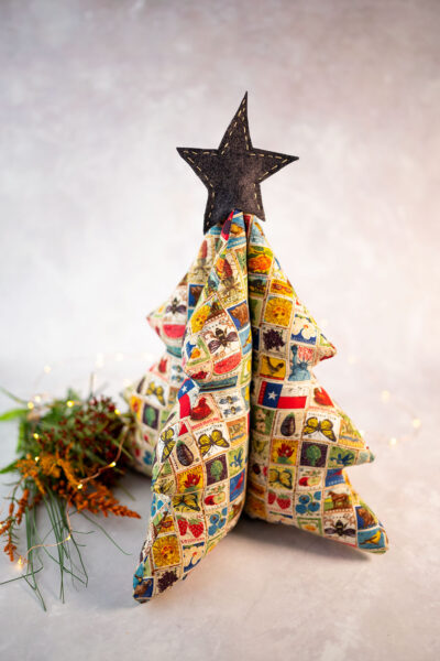 A table top fabric Christmas tree sewn in fabric that looks like vintage postage stamps posed with dried flowers and fairy lights