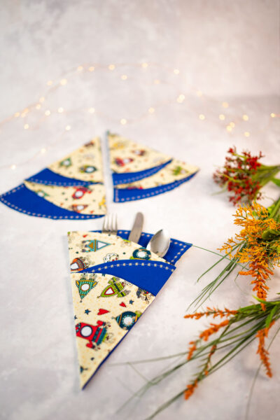 a styled arrangement of 3 Christmas tree napkins demonstrating a place setting with fairy lights in the background
