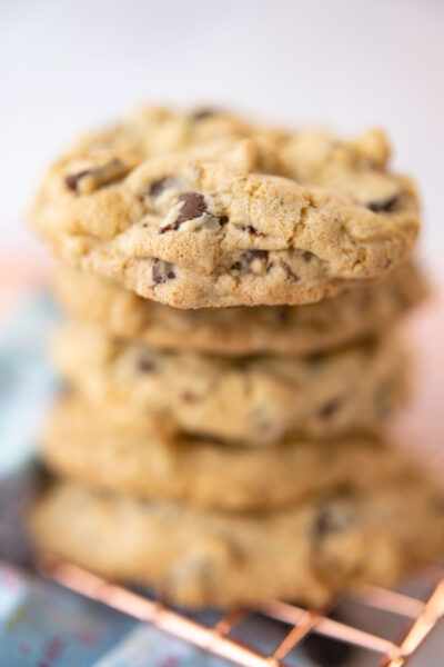closeup of a stack of fresh baked chocolate chip cookies on a copper rack