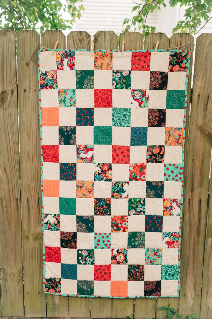 A patchwork finished quilt is displayed on a wooded fence.