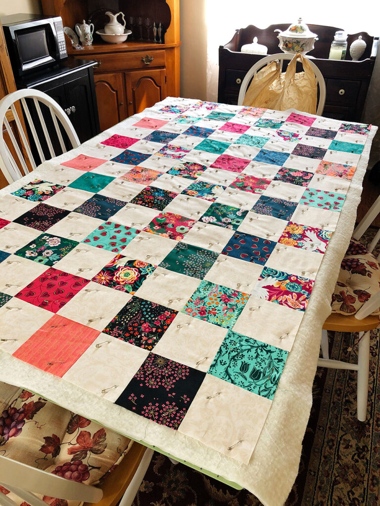 A patchwork quilt top is laid out flat on a table pin basted to the batting and backing.