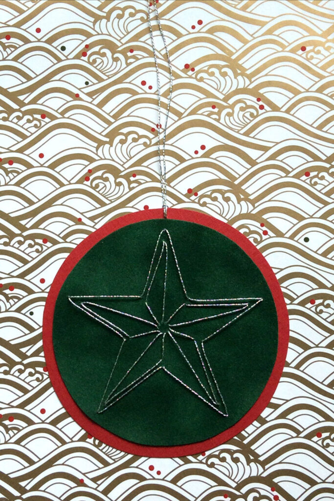 Round gift tage hand stitched on paper with red and green paper and a silver star