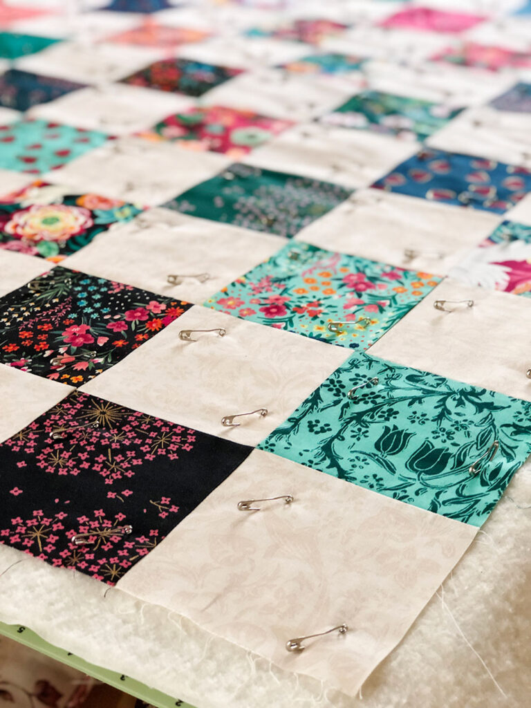 Closeup of a patchwork quilt that is pin basted to the batting and backing material.