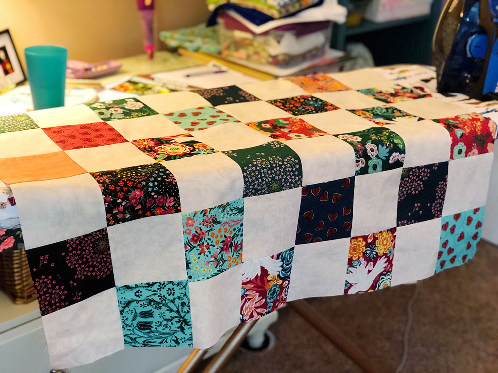 A partially sewn quilt top is spread across an ironing board.