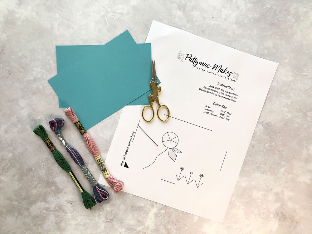 Overhead view of the supplies needed to make the project which includes card stock, embroidery floss, needle, scissors and the free pattern