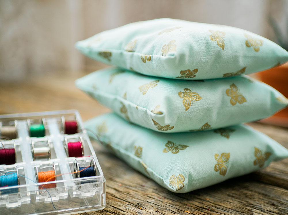 Three blue dream pillows stacked next to a case of bobbins with different thread colors