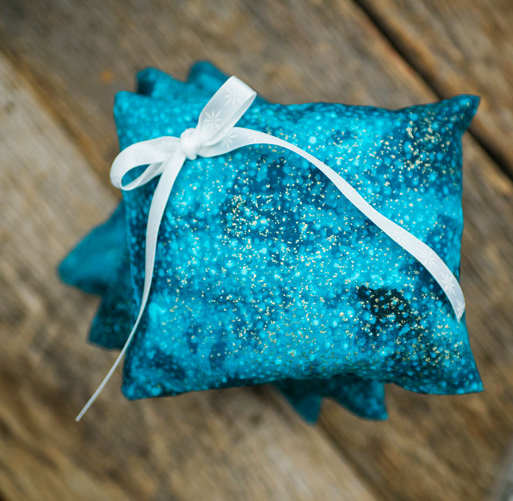 closeup view of a bright blue pillow with a white bow.