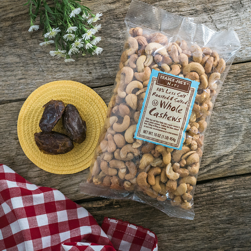 overhead view of a bag of roasted cashews from Trader Joe's and 3 medjool dates