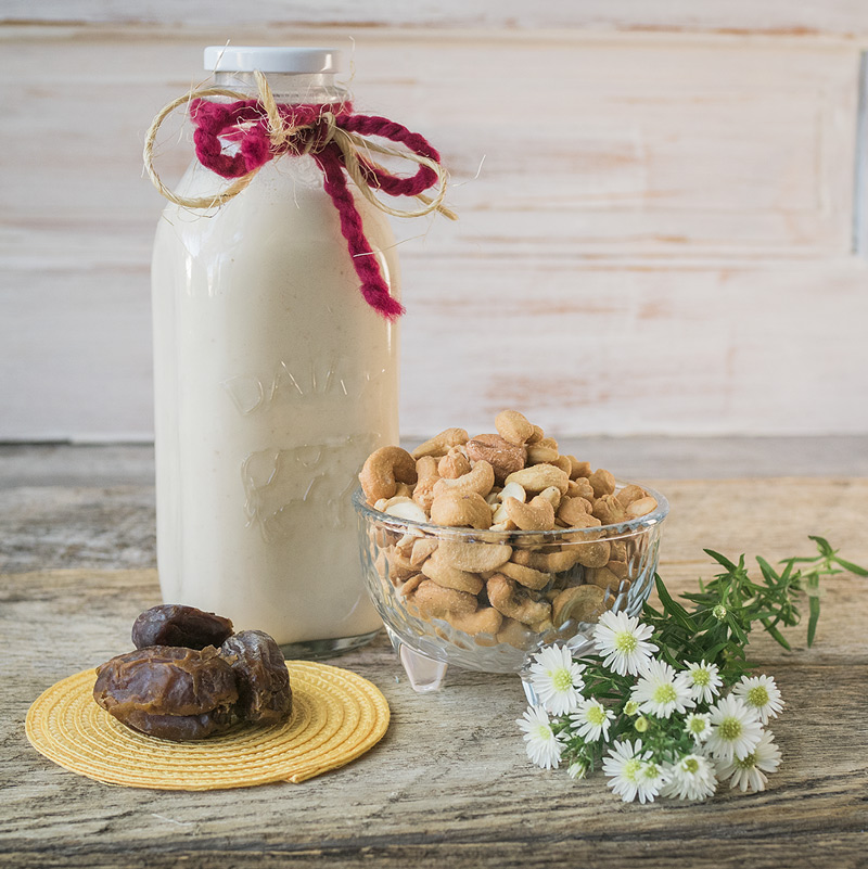 a bottle of chilled cashew milk sits with the ingredients used to make it, roasted cashews and medjool dates