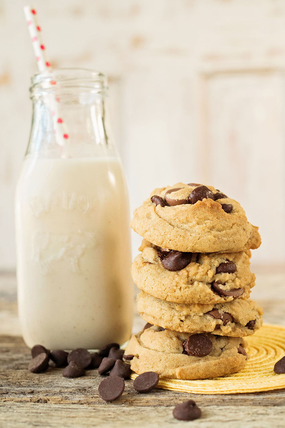 stack of 4 vegan chocolate chip cookies with a small milk bottle of cashew milk