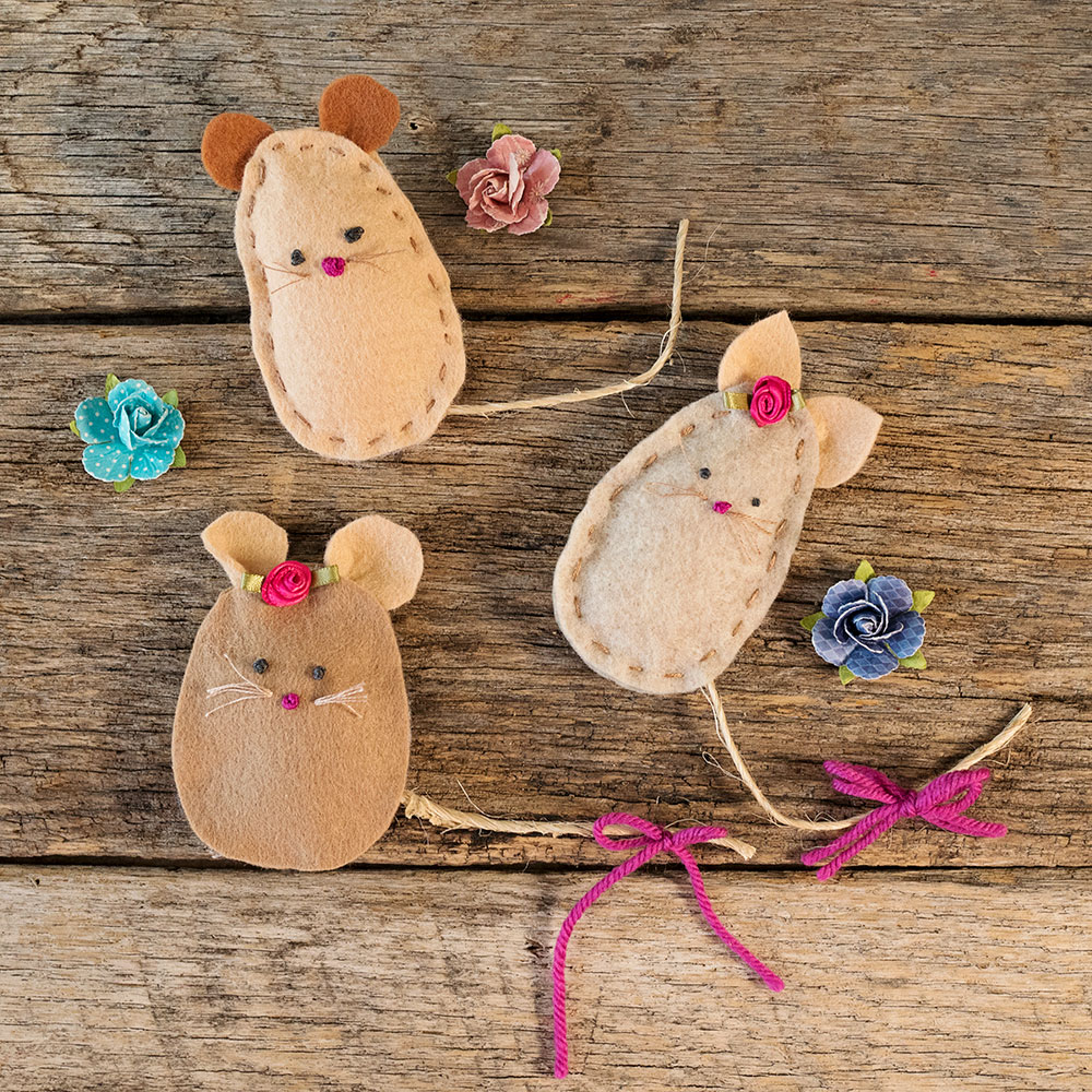 overhead view of a felt mouse family with a hand stitched faces posed next to paper roses
