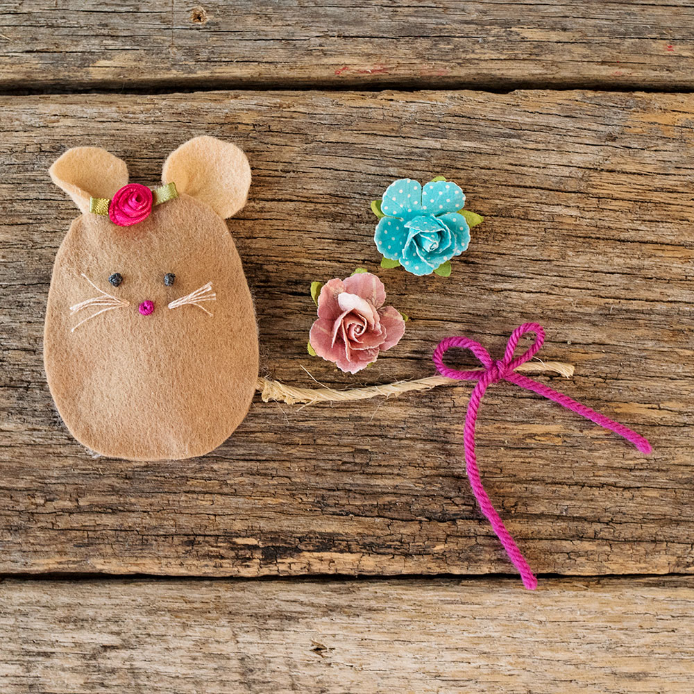 overhead view of a felt mouse with a hand stitched face posed next to paper roses